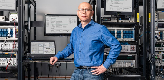 A semiconductor systems engineer at NI stands in front of racks equipped with PXI systems.