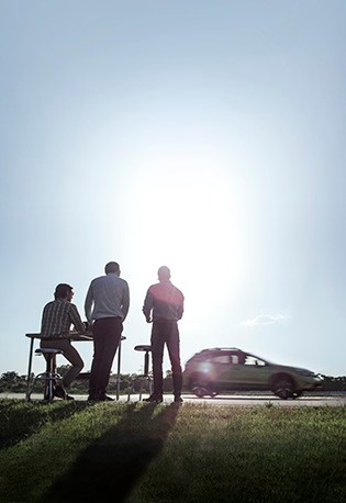 A team of engineers conduct hardware-in-the-loop test on a Subaru hybrid vehicle outside on the road