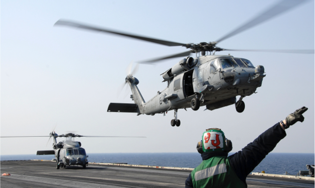 An air traffic controller directs helicopters taking off from an aircraft carrier.