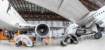 Two commercial jets side by side in a hangar