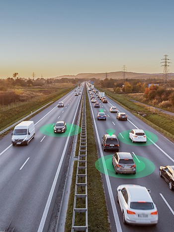 Autonomous vehicles drive alongside people in their cars on a four-lane highway at sunset