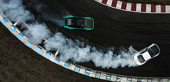 Aerial view of cars turning corner on race track with exhaust trailing behind
