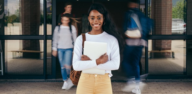 A STEM student stands outside of her school, smiling. Classmates enter and exit the building behind her.