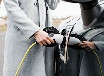 A driver charges her electric vehicle.