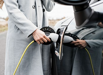 A driver charges her electric vehicle on the side of the road.