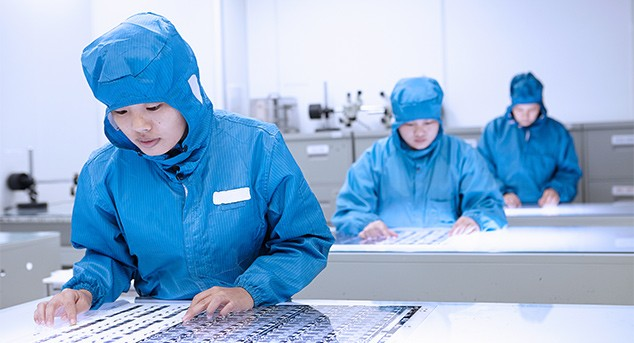 Researchers wearing blue protective garments working in a laboratory.