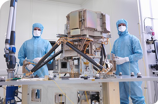 Two engineers wearing blue protective garments work on line replaceable units on a satellite in a lab