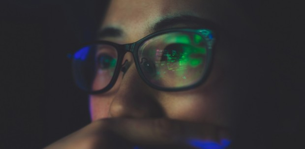 Data from a computer monitor is reflected in a validation engineer's glasses.