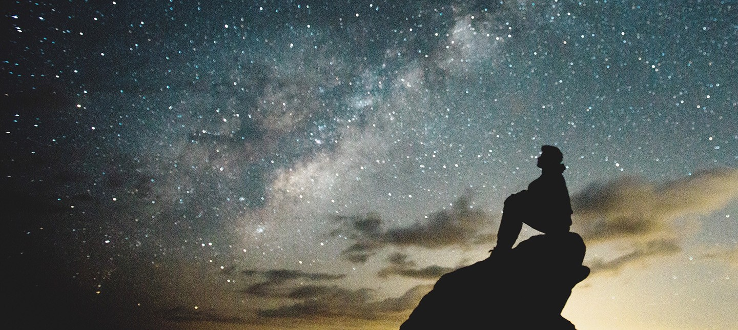 A young person sitting on a hill is in silhouette observing the stars in the night sky