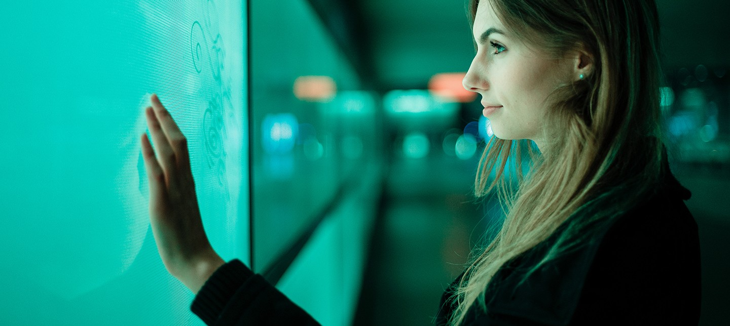 An engineer touches a screen. The green glow illuminates her face.