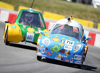 Drivers race energy efficient vehicles around the track during the Shell Eco-marathon.