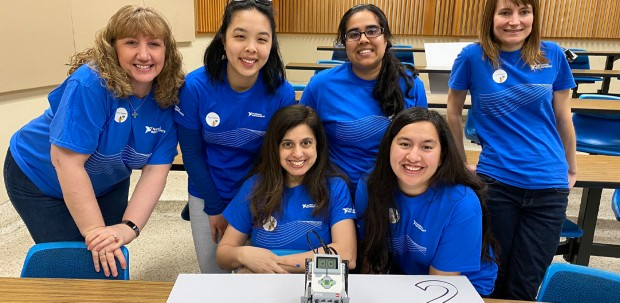 Girl Day engineering mentees smile for the camera with a robotic puppy.