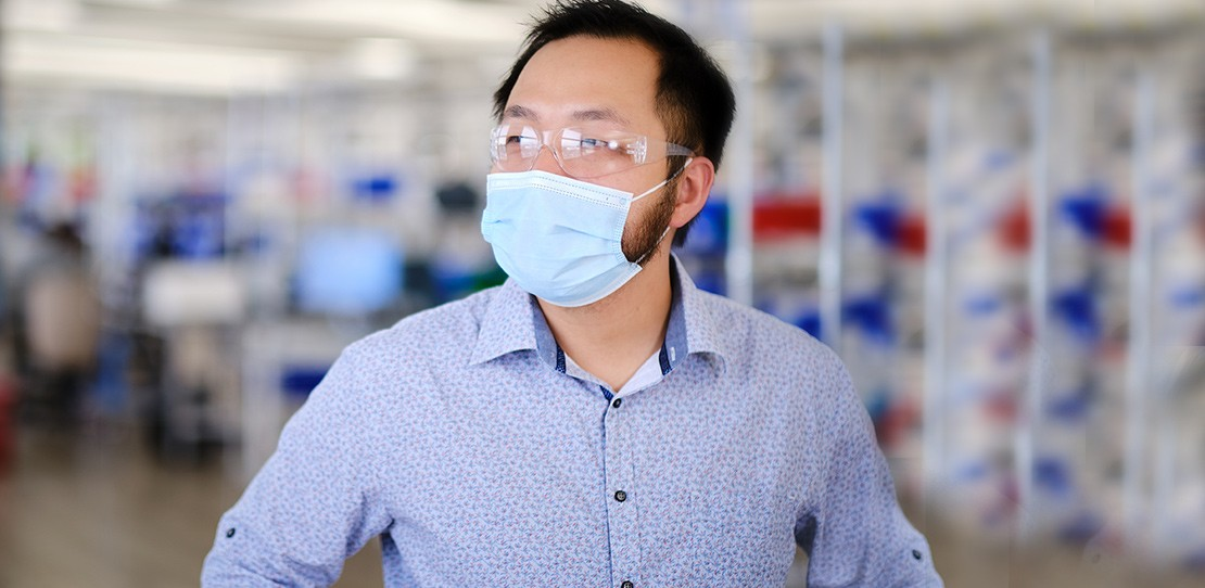 David Weng, lead developer at Velentium, stands on the production floor wearing a mask.