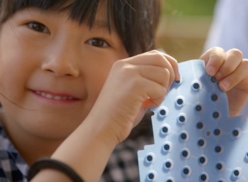 Close up of smiling girl learning the basics of engineering.