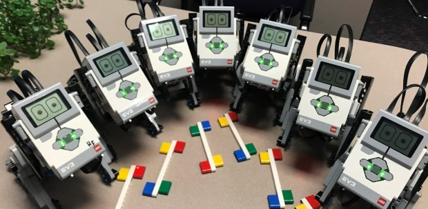 A row of seven robotic puppies on a classroom table.