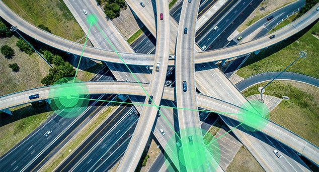 Aerial view of highway with illustration showing cars communicating over 5G signals