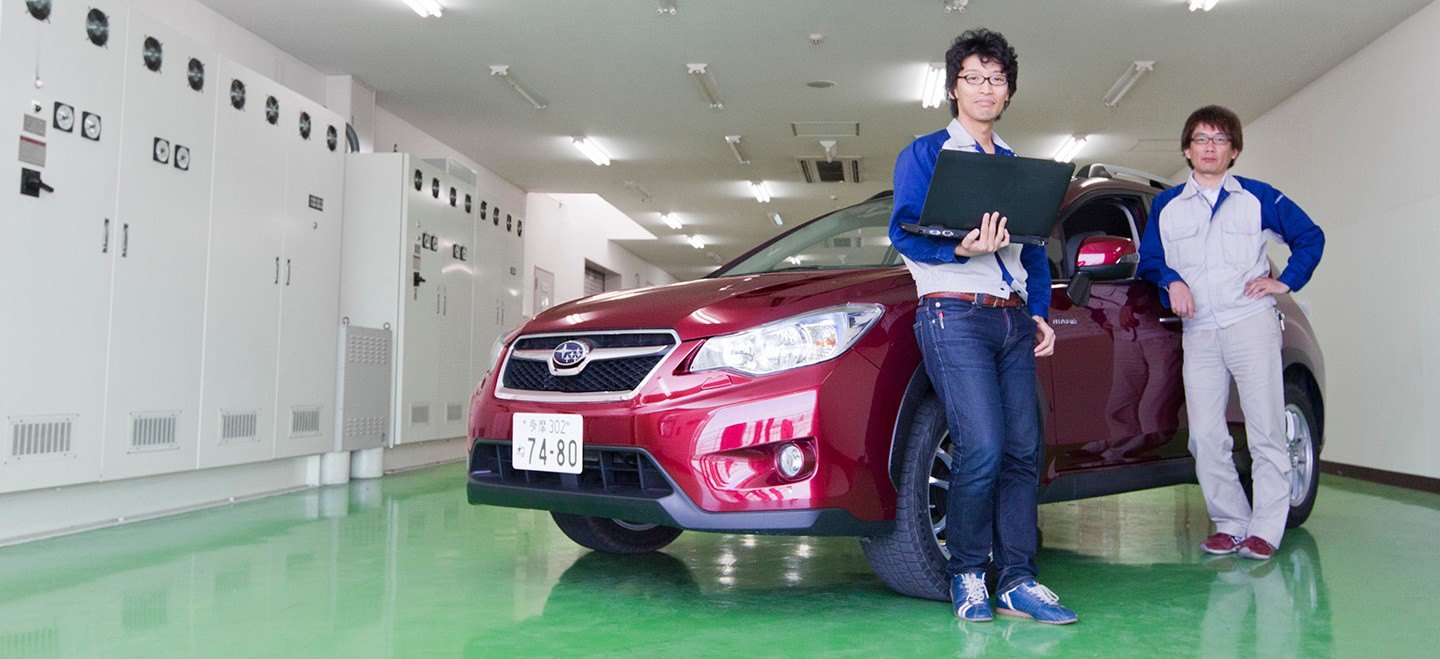 Two test engineers from Subaru lean on a hybrid car.