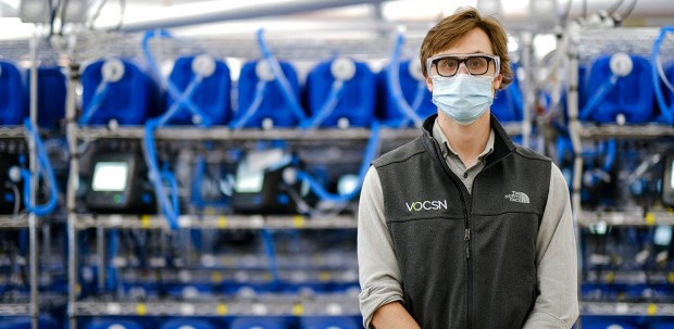 Sam Burner, manufacturing engineer at Ventec Life Systems, stands in front of shelves full of ventilators. He is wearing a face mask and eye protection.