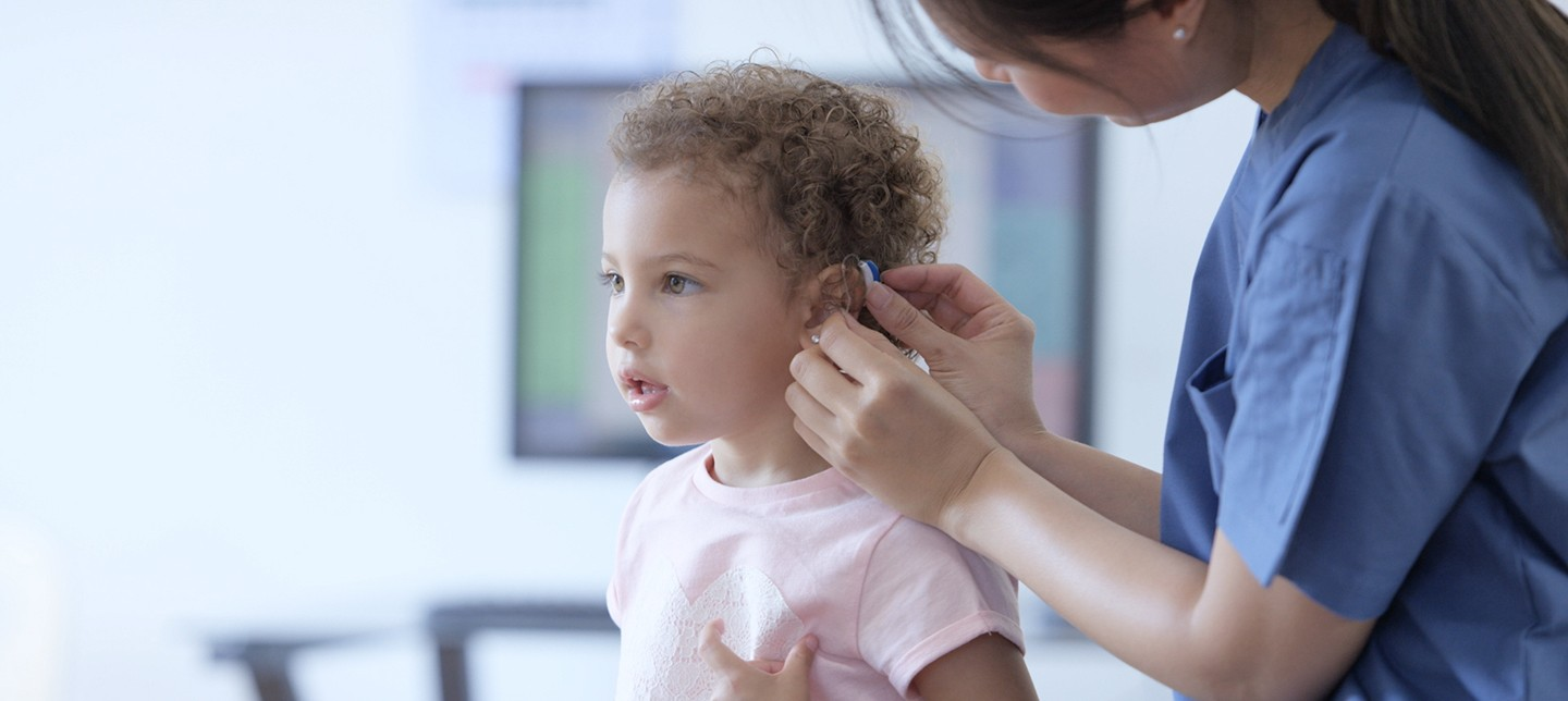 A doctor fits a young girl with a hearing device containing a small, long-lasting battery.