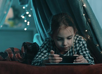 A child watches videos on her phone in a blanket fort decorated with LED string lights.